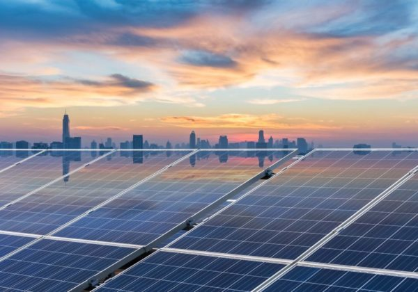 sunset glow reflected on solar panels with bangkok skyline